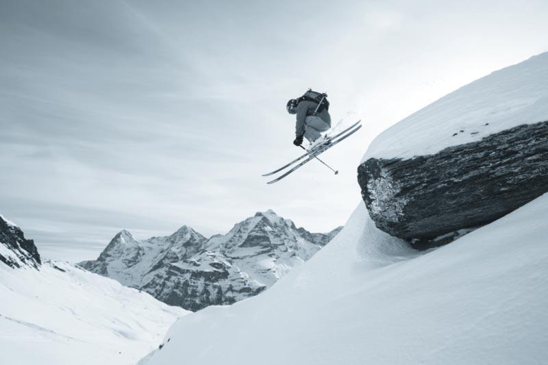 Skifahrer springt über Felsen